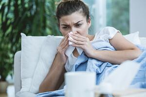 Sick woman with runny nose lying in bed